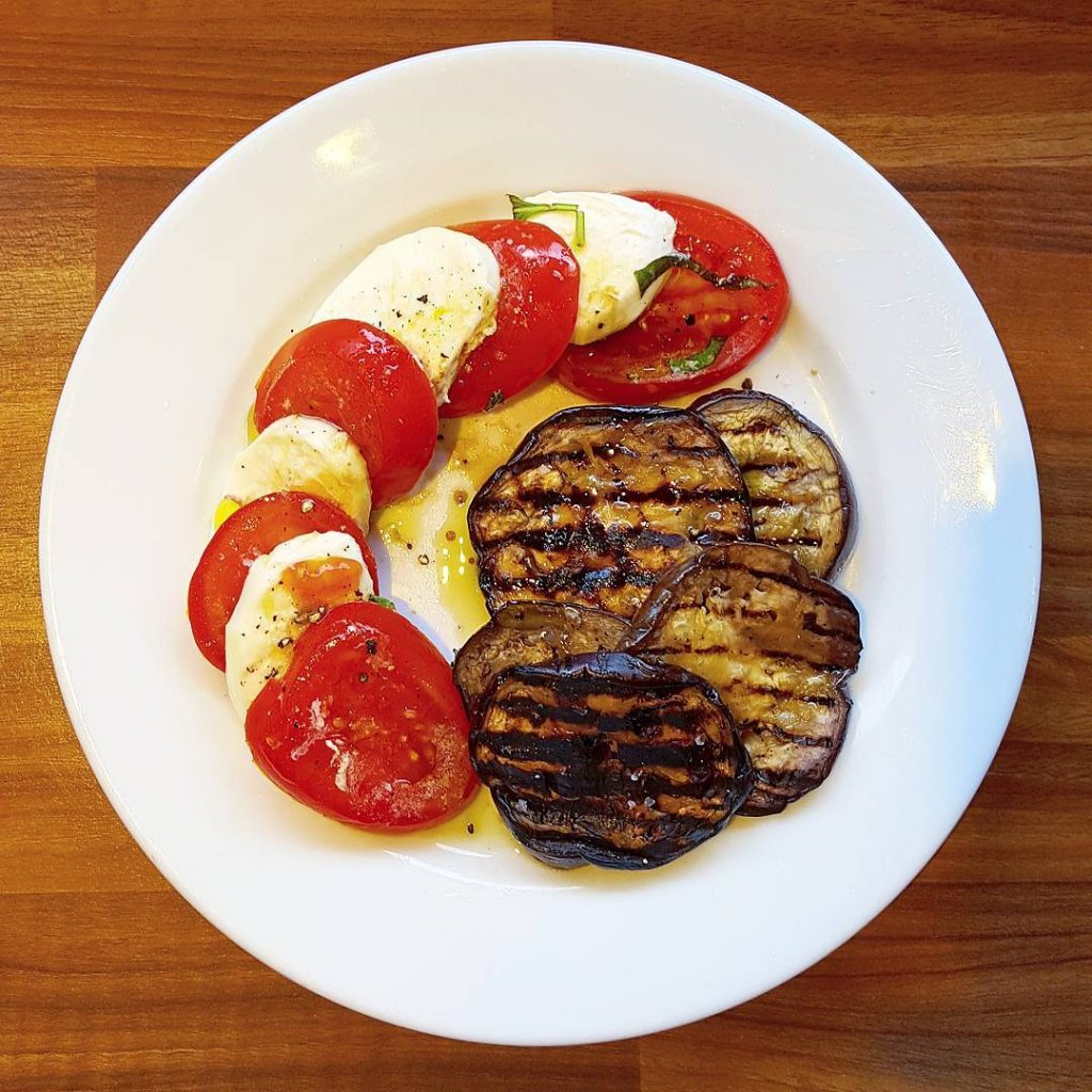 Simple but deliciouschargrilled aubergine with tomato and buffalo mozzarella