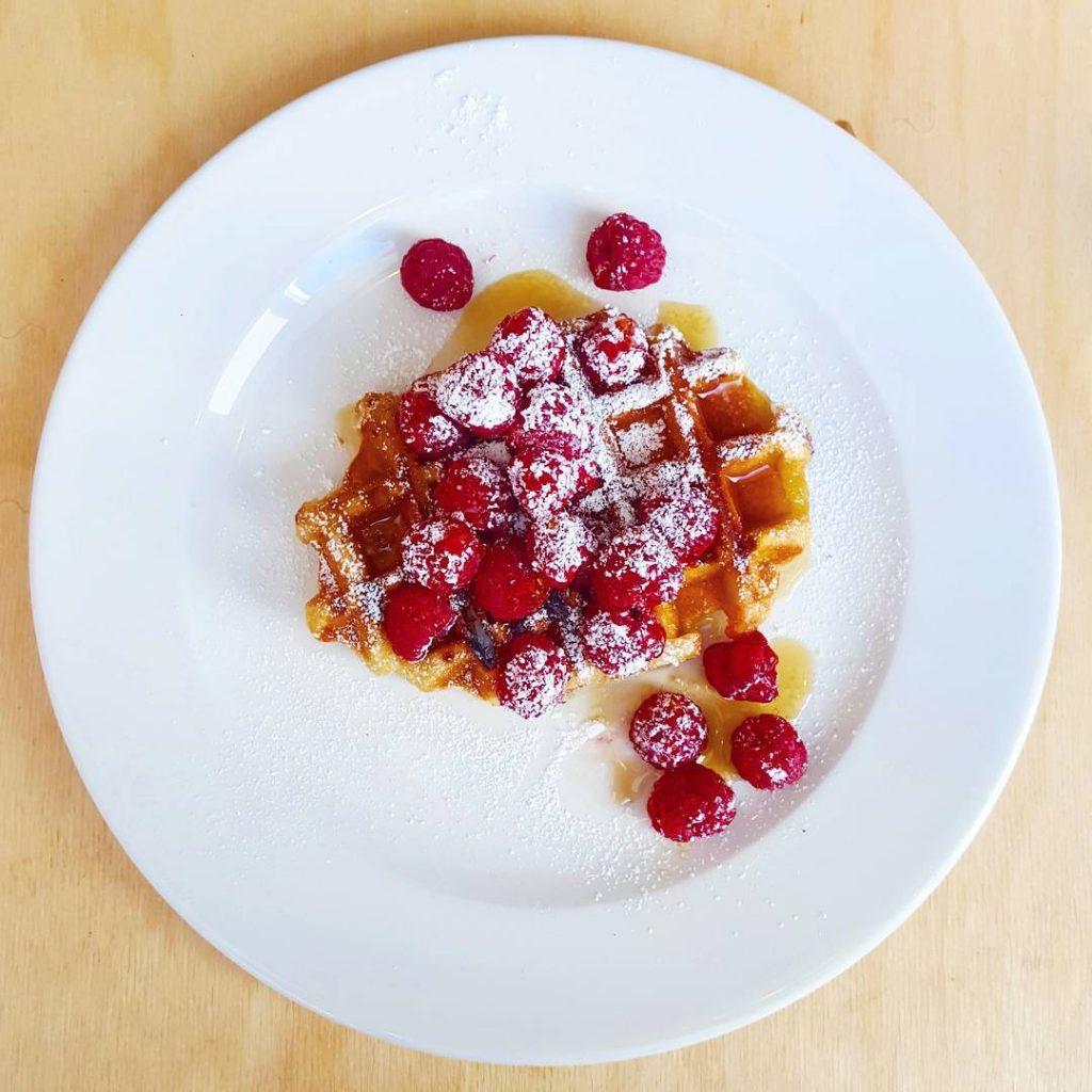 Waffles raspberries and maple syrup at southsideroasters