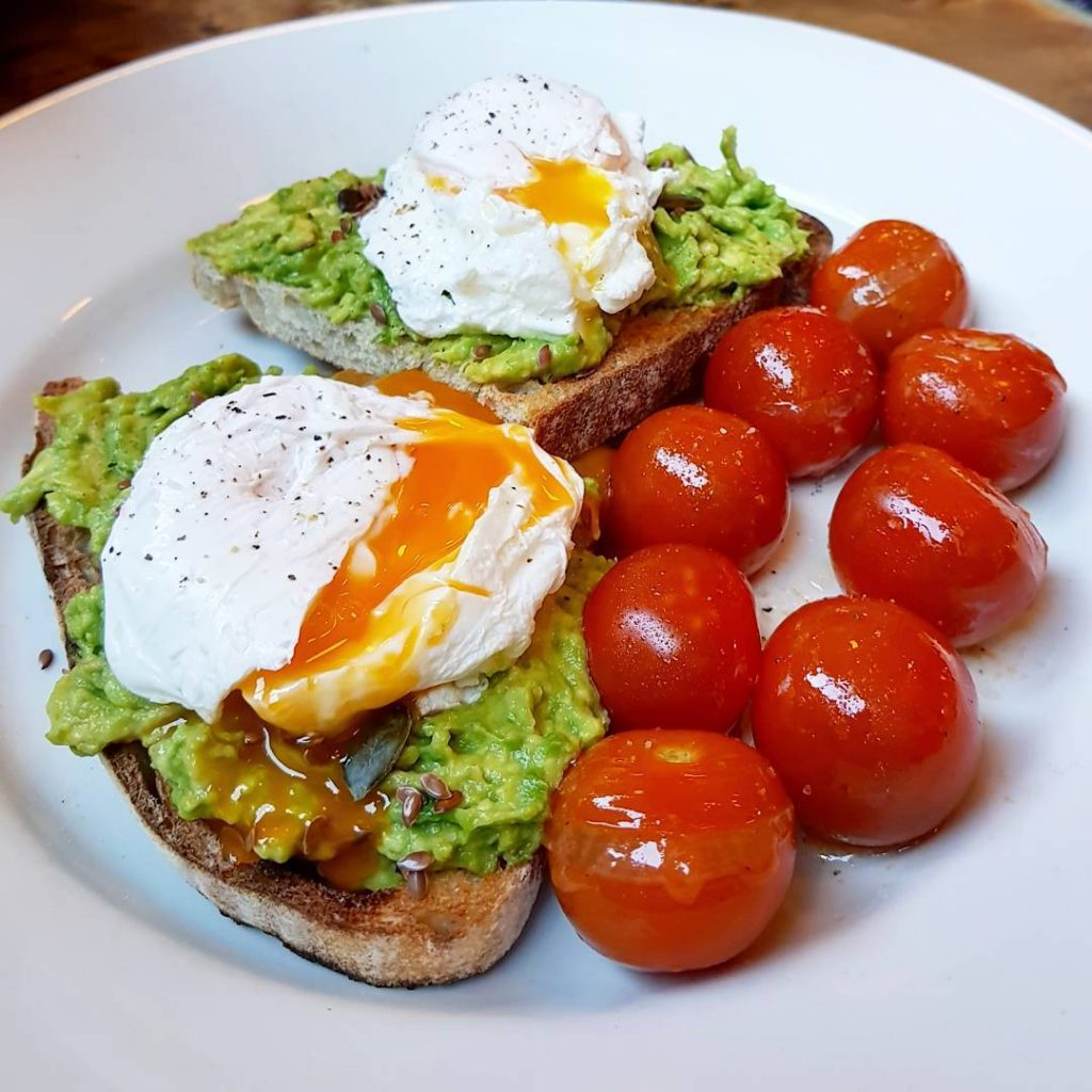 Avocado toast with poached eggs and roasted tomatoes at cafegandolfi